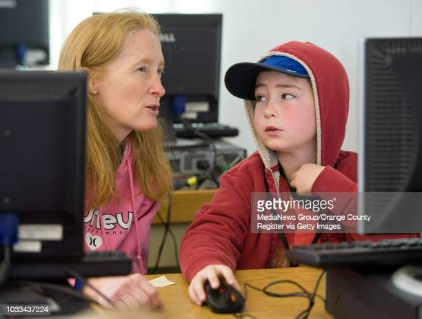 Rossmoor Elementary fourthgrader Luke Goldade works on a Powerpoint presentation with his mom Debbie The school's media center is open to parents and...