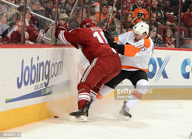 Rostislav Klesla of the Phoenix Coyotes battles for a loose puck with Chris VandeVelde of the Philadelphia Flyers at Jobingcom Arena on January 4...