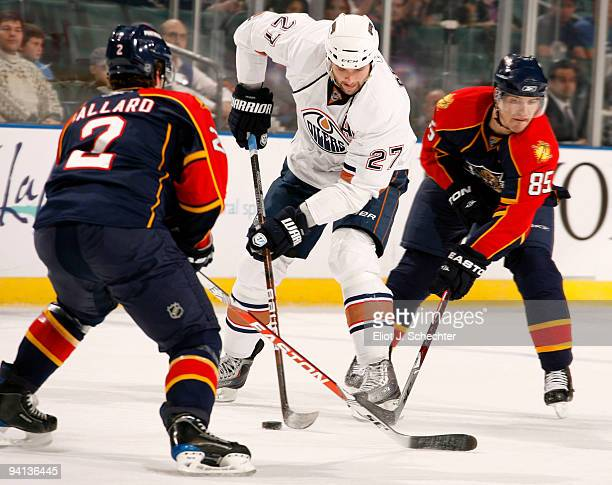 Rostislav Olesz of the Florida Panthers and teammate Keith Ballard battle for the puck against Dustin Penner of the Edmonton Oilers at the...