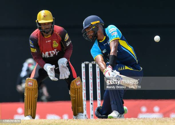 Roston Chase of Saint Lucia Kings hits 4 and Denesh Ramdin Trinbago Knight Riders watch during the 2021 Hero Caribbean Premier League Play-Off match...