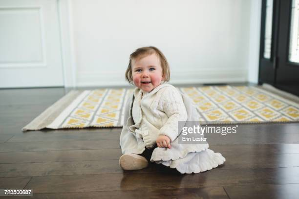 Rosy-cheeked baby sitting on the floor smiling
