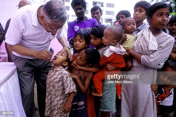 Rotarian Iftekharul Alam administers the oral polio vaccine to children from the sweepers colony slum in Dhaka April 23, 2000 during the Polio...