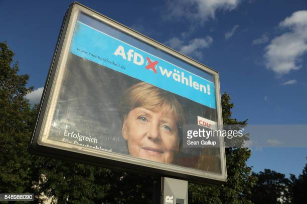 Rotating billboards show an election campaign poster of German Chancellor and Christian Democrat Angela Merkel intersecting with one of the rightwing...