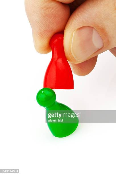 Rote und grüne Spielfiguren Mobbing Rauskicken Wettbewerber
