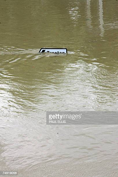 A road sign pointing to the village of Treeton is almost submerged in flood waters in the Catcliffe area of Sheffield 26 June 2007 as the level of...