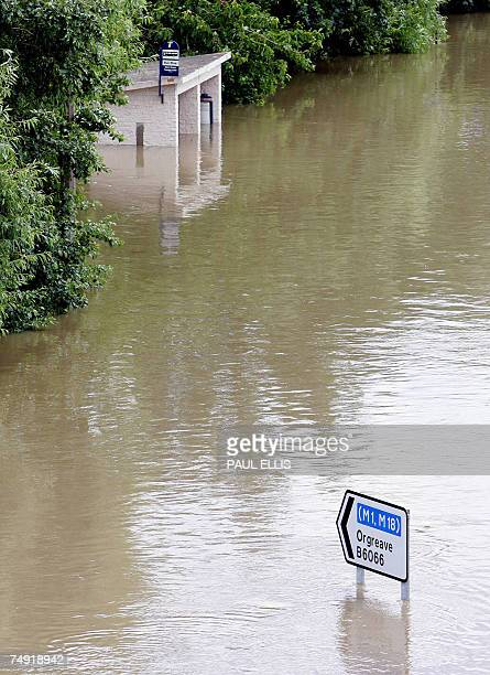 A sign pointing to the M1 motorway is seen on the main road through the Catcliffe area of Sheffield submerged in flood waters 26 June 2007 as the...