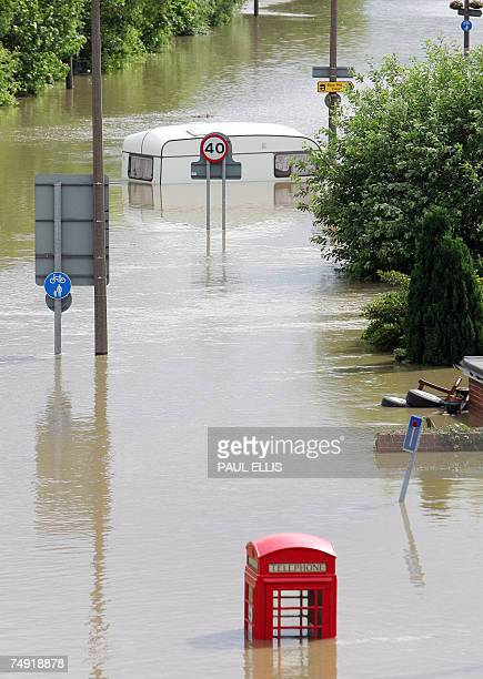A telephone kiosk and a caravan are seen in flood waters in the Catcliffe area of Sheffield 26 June 2007 as the level of river water continued to...