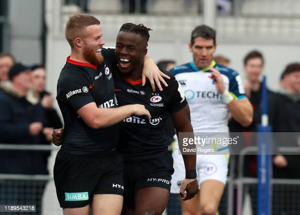 Rotimi Segun of Saracens celebrates with team mate Tom Whiteley after after scoring their bonus point winning fourth try during the Heineken...