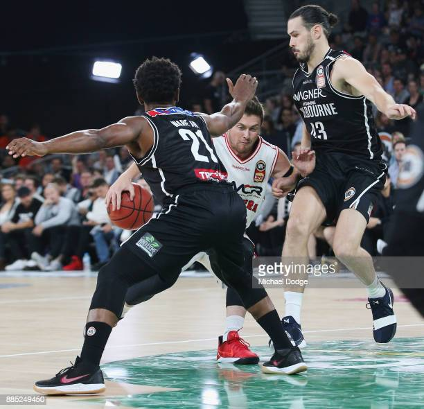 Rotnei Clarke of the Hawks drives hard against Casper Ware and Chris Goulding of United during the round eight NBL match between Melbourne United and...