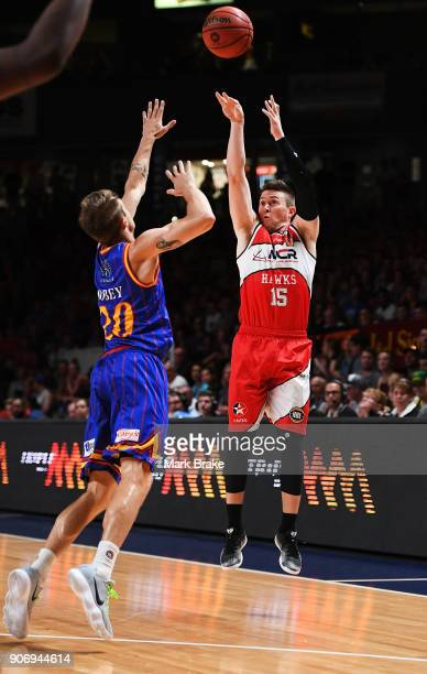 Rotnei Clarke of the Illawarra Hawks shoots for three over Nathan Sobey of the Adelaide 36ers during the round 15 NBL match between the Adelaide...
