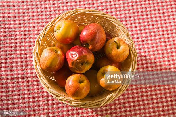 Rotten apple among good ones in basket on table