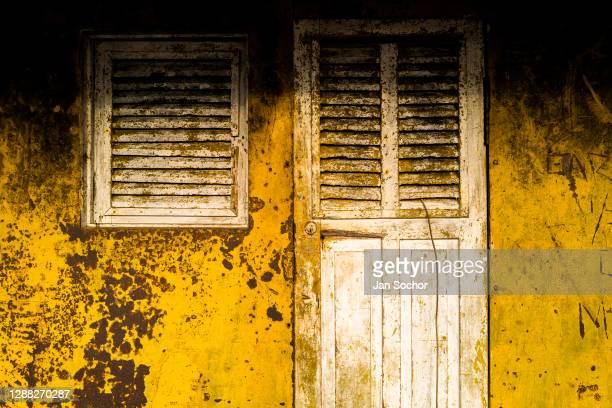 Rotten window next to a rotten cabin's door are seen on the deck of an old gold dredge anchored in the Atrato river on October 12, 2019 in Quibdó,...