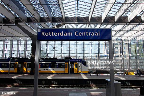 Rotterdam Centraal sign on platform with NS Sprinter train in background Glass roof with solar panels