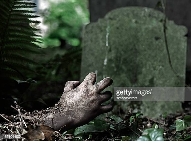A rotting hand reach out from under the grave