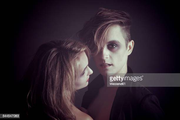 Rouged couple in front of dark background