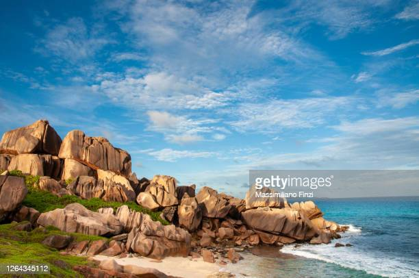 rough and wild rocky coastline at anse songe with lush green grass, tropical vegetation, red granite rocks on the waterfront of the indian ocean. la digue island, seychelles - cor saturada - fotografias e filmes do acervo