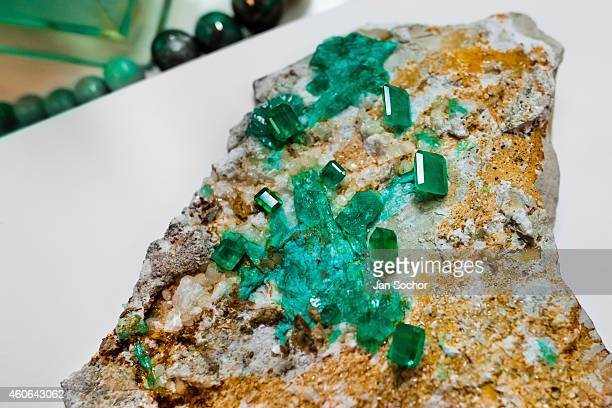 A rough emerald gemstone together with the polished stones are seen in a jewelry workshop on February 08 2014 in Bogota Colombia Around 60% of the...