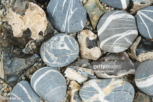 Rough flint stones and round granite pebbles,  close-up, full frame