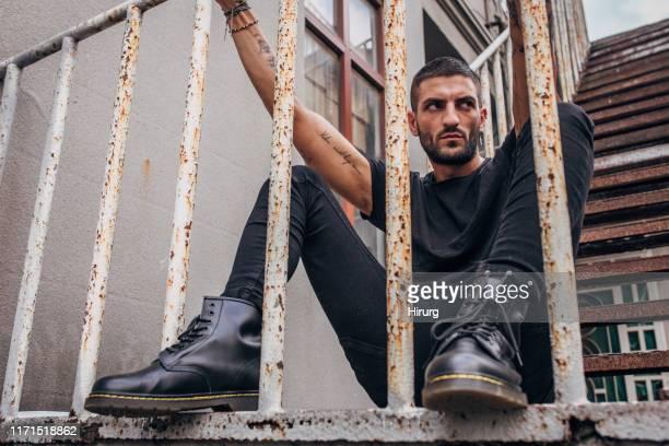 type rugueux dans la tenue noire - bottes noires photos et images de collection