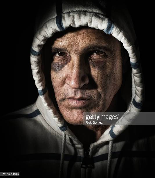 rough looking guy with two black eyes wearing a hoodie and looking intensely at the camera - ugly black men stock photos and pictures