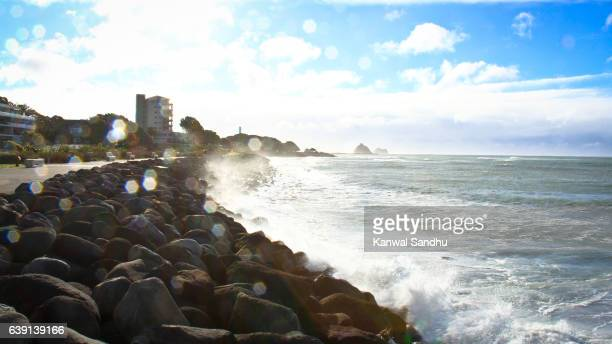 Rough New Plymouth beach with ocean waters splashing boulders