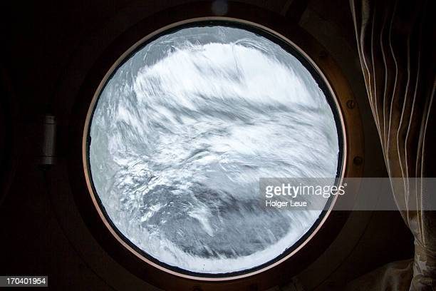 Rough sea seen through porthole of cruise ship