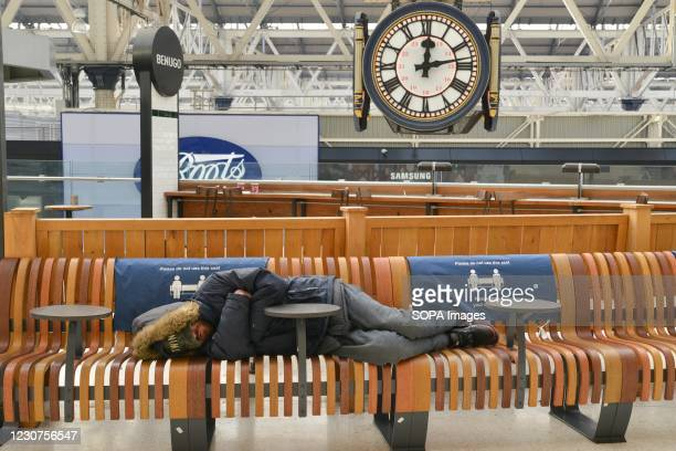 Rough sleeper lies on the bench at the waiting area, at an almost empty London Waterloo railway station. Prime Minister Boris Johnson announced that...