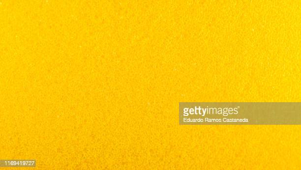rough texture of yellow sponge with holes - foam material stock pictures, royalty-free photos & images