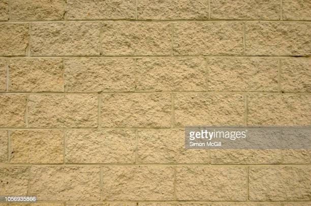 rough textured sandstone block brick wall - sandstone stock pictures, royalty-free photos & images