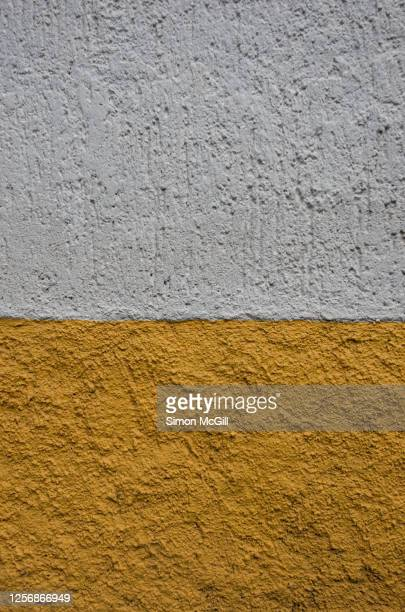 rough, uneven stucco wall painted half white and half yellow - ツートンカラー ストックフォトと画像