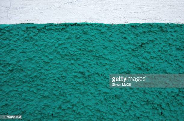 rough, uneven stucco wall painted white and teal green - ツートンカラー ストックフォトと画像