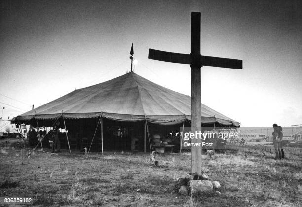 Rough wood cross marks entrance to huge revival tent where Christ is the Answer is having nightly meetings in south Denver The youthful group also...