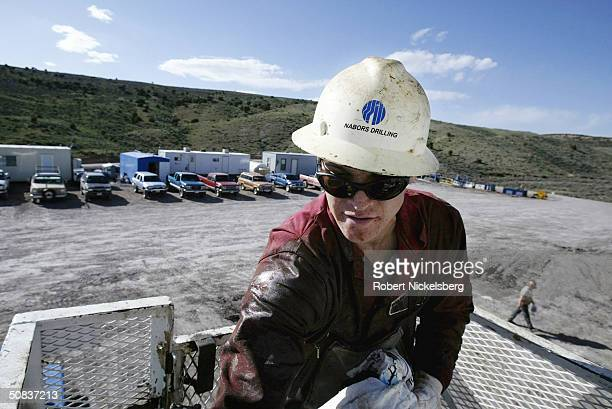 A roughneck leaves the drilling platform by a small elevator after a 12hour shift May 7 2004 eight miles north of Evanston Wyoming Pickup trucks are...