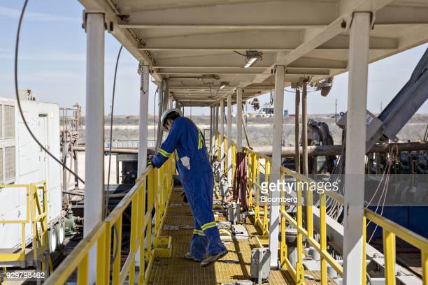 A roughneck walks on a Nabors Industries Ltd drill rig as it is used to drill an oil well for Chevron Corp in the Permian Basin near Midland Texas US...