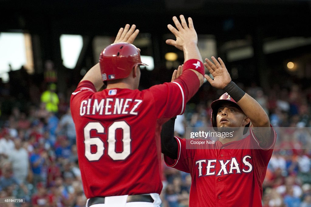Rougned Odor #73 and Chris Gimenez #60 of the Texas Rangers celebrate after scoring on a Dan Robertson #19 double during the second inning against the Houston Astros on July 9, 2014 at Globe Life Park in Arlington in Arlington, Texas.