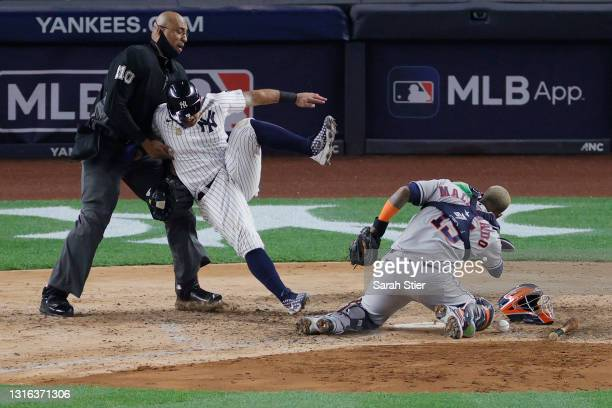 Rougned Odor of the New York Yankees collides with Martin Maldonado of the Houston Astros and home plate umpire Jose Navas during the sixth inning at...