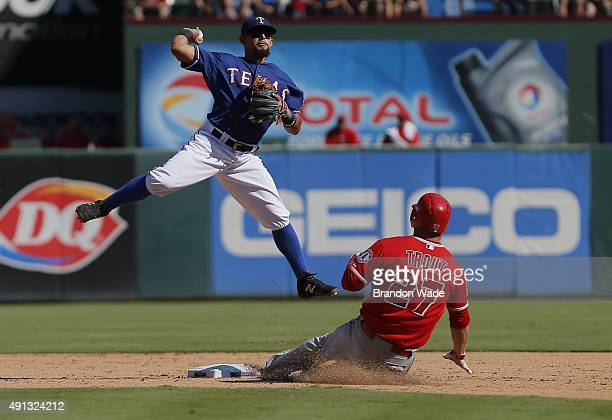 Rougned Odor of the Texas Rangers attempts a throw to first after forcing out Mike Trout of the Los Angeles Angels during the sixth inning of a...