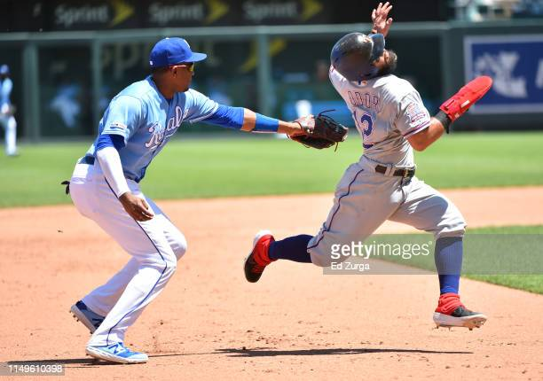Rougned Odor of the Texas Rangers avoids a tag by third baseman Kelvin Gutierrez of the Kansas City Royals as he tries to advance to third in the...