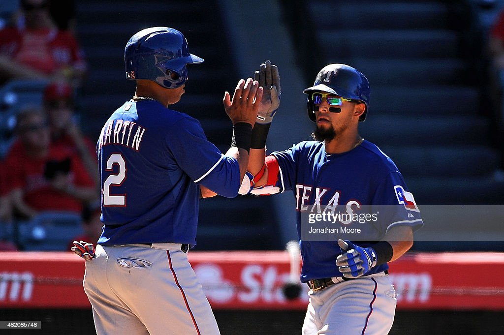 Rougned Odor #12 of the Texas Rangers celebrates with Leonys Martin #2 after hitting a two run home run in the ninth inning during a game against the Los Angeles Angels of Anaheim at Angel Stadium of Anaheim on July 26, 2015 in Anaheim, California. The Angels beat the Rangers 7-13.