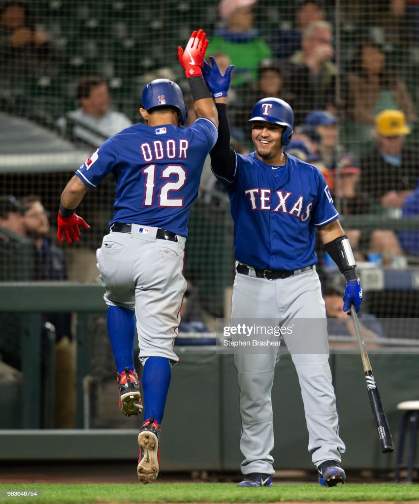 Rougned Odor #12 of the Texas Rangers is congratulated by Carlos Perez #60 after scoring on a double by Carlos Perez #60 off of relief pitcher Edwin Diaz #39 of the Seattle Mariners during the ninth inning of a game at Safeco Field on May 29, 2018 in Seattle, Washington. The Rangers won the game 9-5.