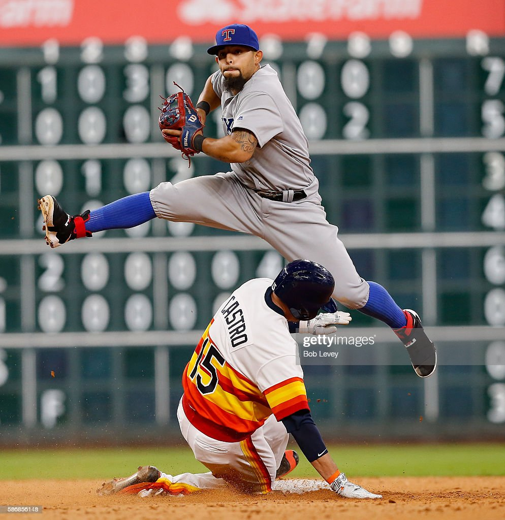 Rougned Odor #12 of the Texas Rangers leaps over Jason Castro #15 of the Houston Astros as he forces him out in the ninth inning at Minute Maid Park on August 6, 2016 in Houston, Texas.