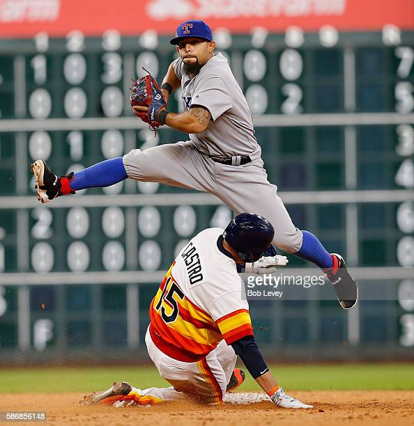 Rougned Odor of the Texas Rangers leaps over Jason Castro of the Houston Astros as he forces him out in the ninth inning at Minute Maid Park on...