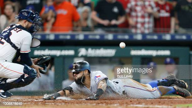 Rougned Odor of the Texas Rangers slides safely into home plate for an inside the park home run as Max Stassi of the Houston Astros is unable to...