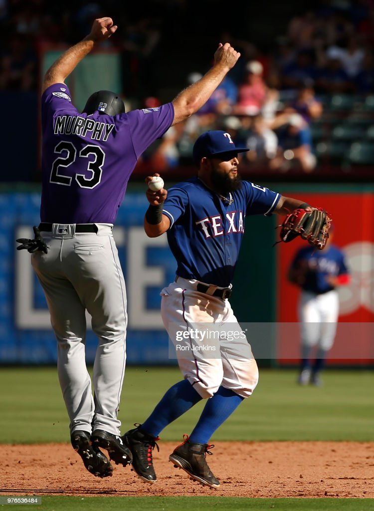 Rougned Odor #12 of the Texas Rangers throws to first base after putting the tag on base runner Tom Murphy #23 of the Colorado Rockies during the ninth inning at Globe Life Park in Arlington on June 16, 2018 in Arlington, Texas. The Rangers won 5-2.