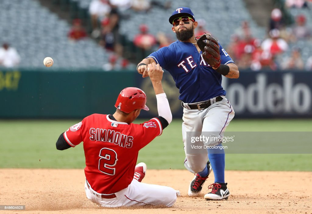 Rougned Odor #12 of the Texas Rangers throws to first base to complete the double play as Andrelton Simmons #2 of the Los Angeles Angels of Anaheim slides into second base during the ninth inning of the MLB game at Angel Stadium of Anaheim on September 17, 2017 in Anaheim, California. The Rangers defeated the Angels 4-2.