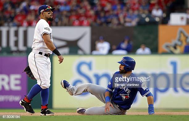 Rougned Odor of the Texas Rangers turns a double play in front of Jose Bautista of the Toronto Blue Jays in game one of the American League Division...