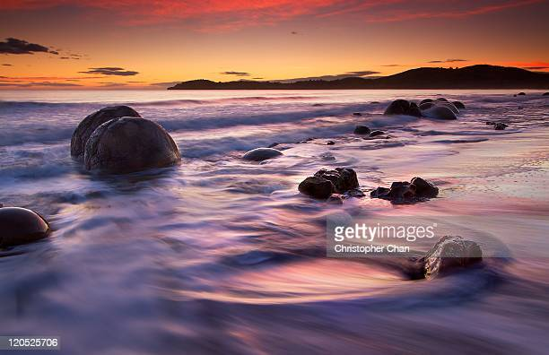 Round boulders on beach at sunrise