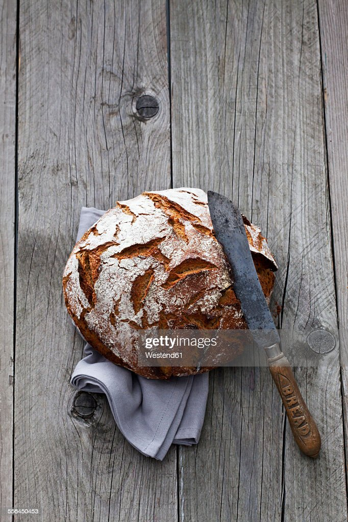Round crusty bread, old bread knife and kitchen towel on wood : Stock Photo
