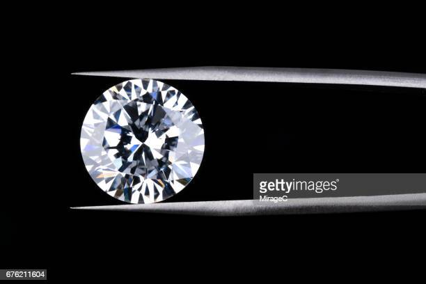 round diamond clamped by tweezers - diamond gemstone stock pictures, royalty-free photos & images