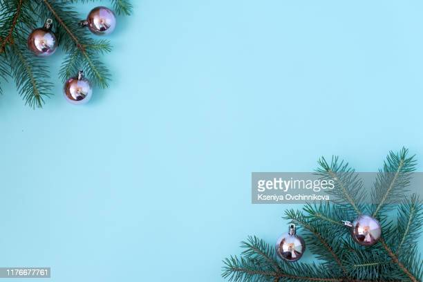 round frame of christmas decorations with copy space on blue background. wreath composition of cones, balls,tree and star. top view, flat lay. - snowflake background stock photos and pictures